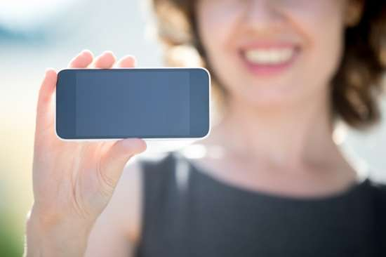 closeup_of_smiling_woman_showing_a_mobile