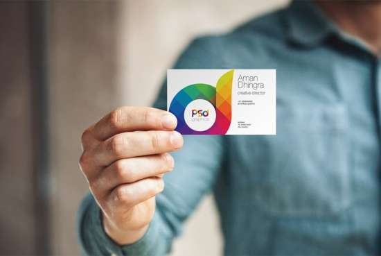man_holding_business_card_mockup_psd